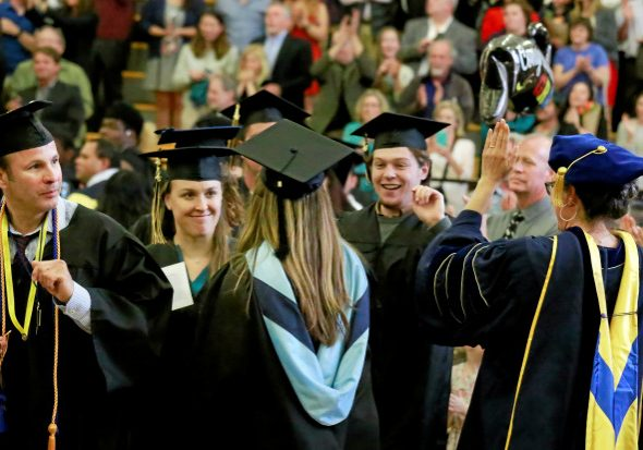 A procession of graduates receive congratulations from teachers as they file into the Diamond Physical Education Center during the commencement ceremony at Collage of Marin in Kentfield, Calif. Friday, May 20, 2016.(James Cacciatore/Special to the Marin Independent Journal)
